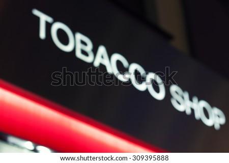 Tobacco shop neon sign - blurred - stock photo