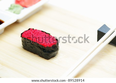 Tobiko sushi on wood with ginger and chopsticks - stock photo