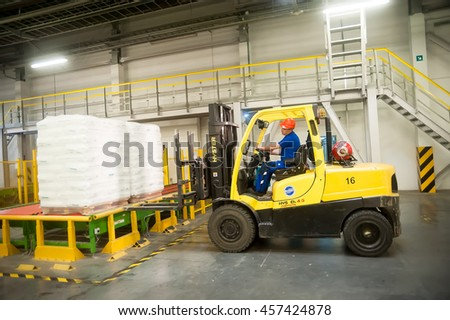 Tobolsk, Russia - July 15. 2016: Sibur company. Central control panel of Tobolsk Polymer plant. Driver on forklift truck loads pallets with finished goods from packaging machine - stock photo