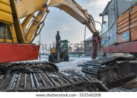 Tobolsk, Russia - March 5, 2009: Excavator construction vehicles working for repair water and sewer pipes in downtown - stock photo