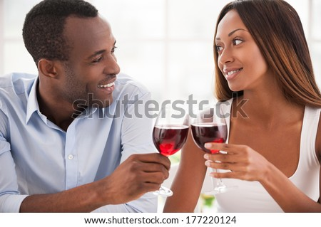 Today is their special date. Beautiful young African couple sitting close to each other and holding wineglasses - stock photo