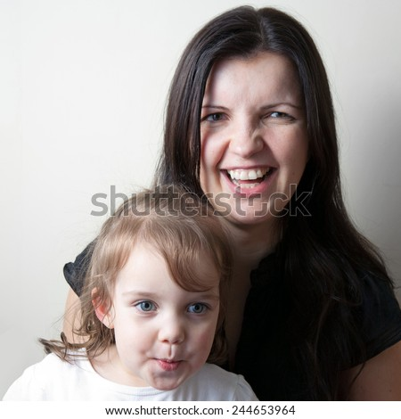 Toddler age girl sitting with her laughing mother while making funny faces. - stock photo