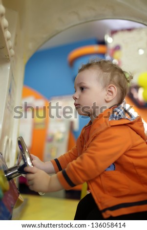 Toddler and amusement car at indoor playground - stock photo