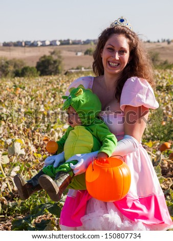 Toddler and his mother dressed up in cute costumes at the pumpkin patch.