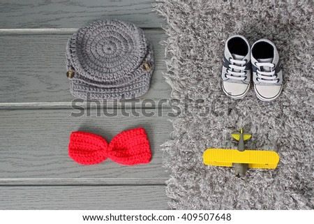 Toddler baby cap, shoes, bowtie and plane lying on the fur blanket with short pile on the wooden floor. Newborn or pregnancy concept - stock photo