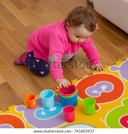 Toddler baby girl plays with colored cups, toy for cognitive development.