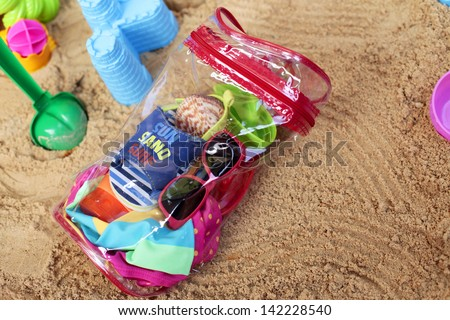Toddler beach bag and toys on beach sand