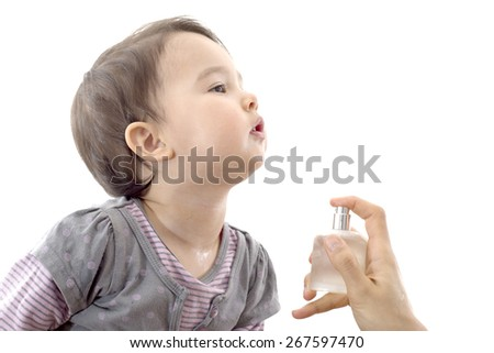 toddler being scented by her mother - stock photo