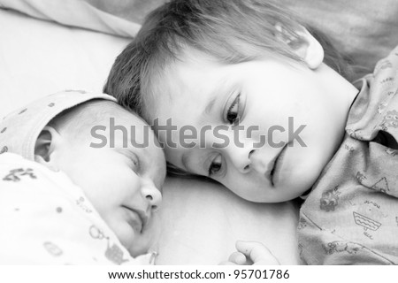 Toddler boy and his newborn sister are lying on a bed. Black  and white photo