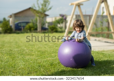 Toddler boy at countryside standing on big ball and having fun on phone mobile - stock photo