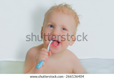 Toddler boy brushing his teeth in bathtub, smiling, light grey background - stock photo