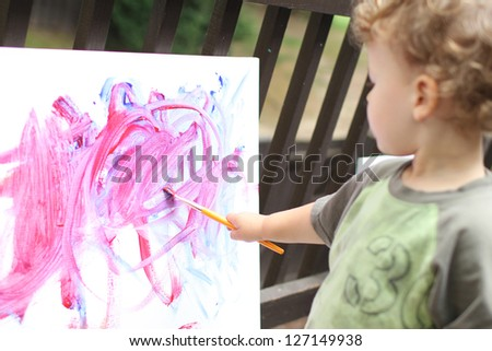 Toddler boy, child, drawing, finger painting, making art - stock photo
