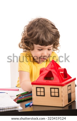 Toddler boy drawing at table isolated on white background - stock photo