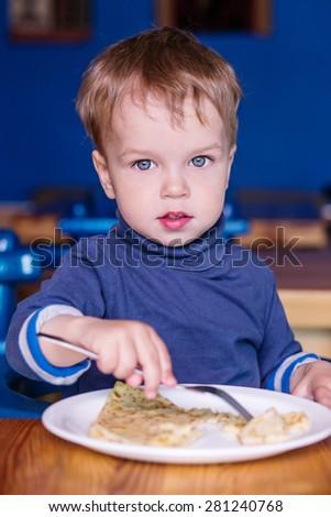 Toddler boy in a cafe eating a pancake - stock photo