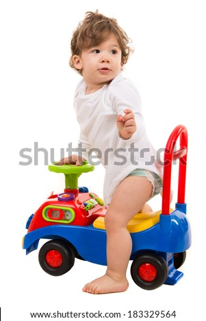 Toddler boy in a car toy looking back isolated on white background