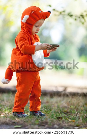 Toddler boy in fox costume holding smartphone - stock photo