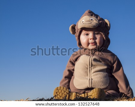 Toddler boy in Halloween costume sitting on bail of hay. - stock photo