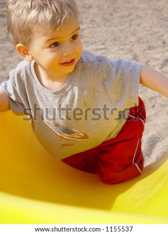 Toddler boy is climbing up the slide at the playground
