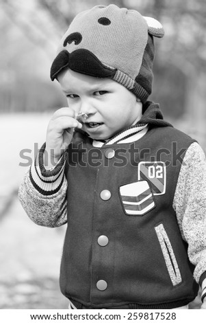 toddler boy is smelling early spring little flower - stock photo