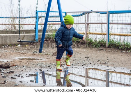 Toddler boy jumping in the puddles in rubber boots