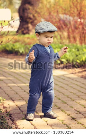 Toddler boy learning to walk outdoors - stock photo