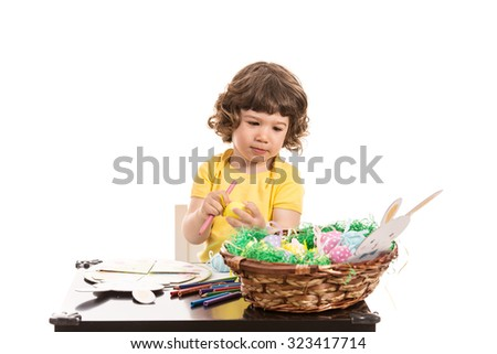 Toddler boy making Easter decorations at kindergarten isolated on white background