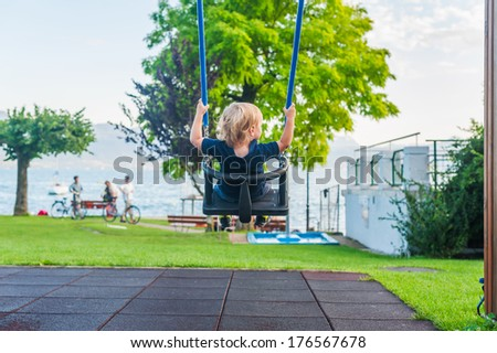 Toddler boy on a swing against beautiful view on a lake - stock photo