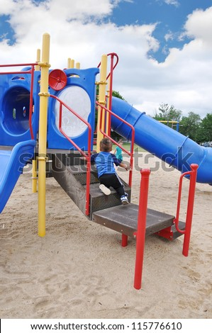 Toddler Boy on Playground Equipment Little girl in background - stock photo