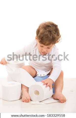 Toddler boy on potty  tear toilet paper against white background - stock photo