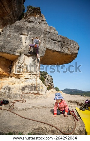 Toddler boy playing at foot of mountain while his mother climbing at the background. The boy is tied in to the rope. - stock photo