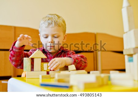 toddler boy playing blocks at the table