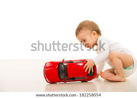 Toddler boy playing with a big red car on the floor against white background