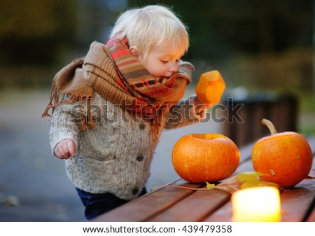 Toddler boy playing with halloween pumpkins, halloween party