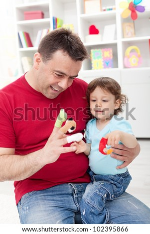 Toddler boy playing with his father at home