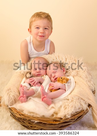 Toddler boy posing with his newborn identical twin sisters - stock photo