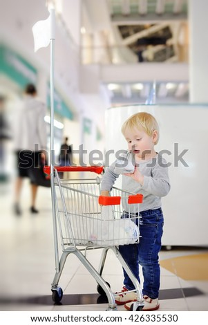 Toddler boy putting purchase in little shopping cart in a shopping mall - stock photo