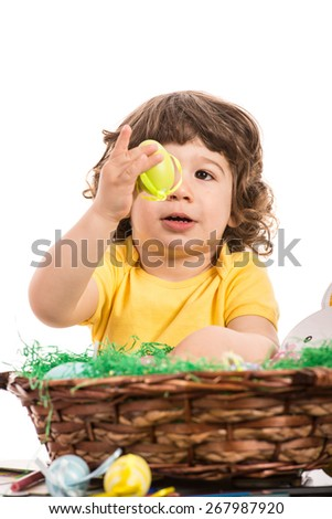 Toddler boy showing and looking at yellow egg from a basket with Easter eggs isolated on white background - stock photo