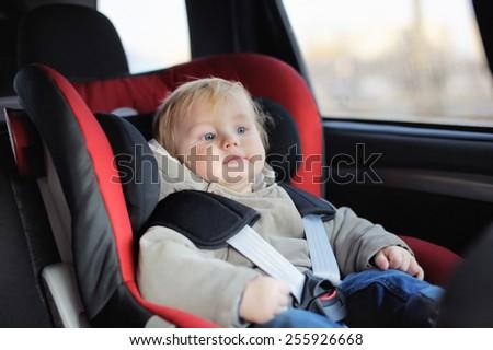 Toddler boy sitting in car seat - stock photo