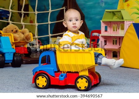 Toddler boy sitting in the toy truck in the game room