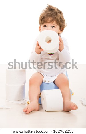 Toddler boy sitting on potty holding rolls paper and looking up