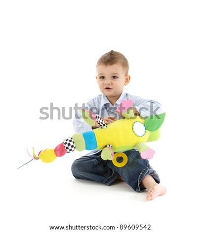 Toddler boy sitting playing with colorful soft toy.?