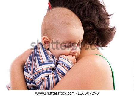 Toddler boy sleeping in his mother's arms - stock photo
