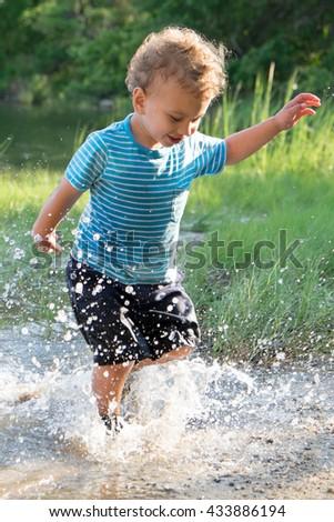 Toddler boy splashing in a pond - stock photo