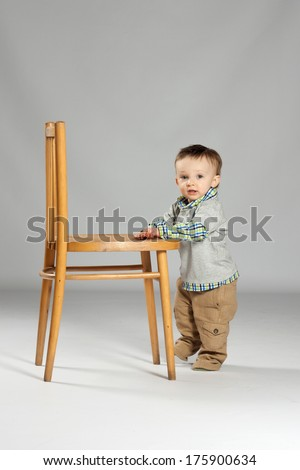 Toddler boy standing beside a big wooden chair - stock photo