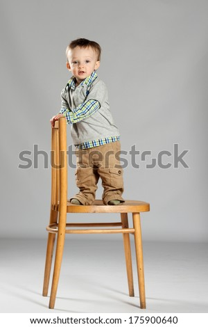 Toddler boy standing on a big wooden chair - stock photo