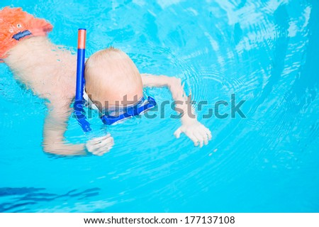 Toddler boy swimming under water in mask and snorkel outdoors - stock photo