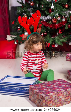 Toddler boy with big reindeer ears sitting under tree  opening gifts and looking away - stock photo