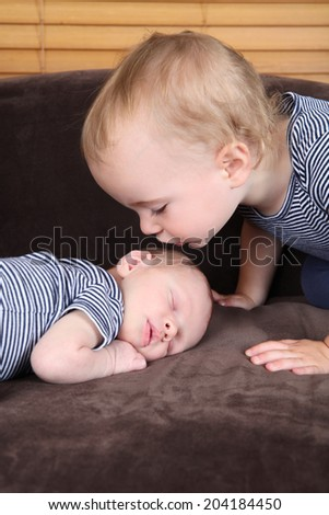 Toddler boy with his newborn baby brother - stock photo