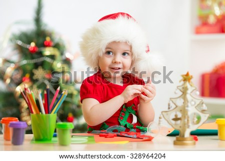 Toddler child girl making by hands christmas decorations - stock photo