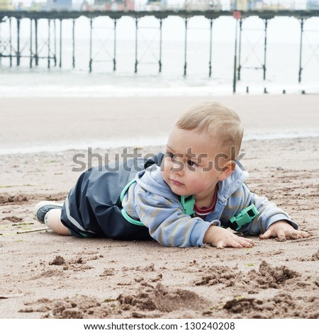 Toddler child in waterproof clothes playing with sand on beach; Teignmouth, Devon, England, UK.